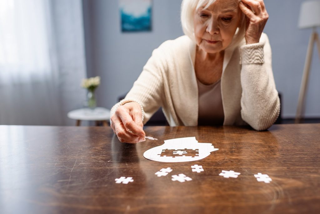 Senior woman with Vasular dementia completing a puzzle for dementia therapy