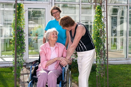 A smiling elderly woman in a wheelchair looks up and takes the hand of another woman, while a smiling memory care facility caregiver looks on.